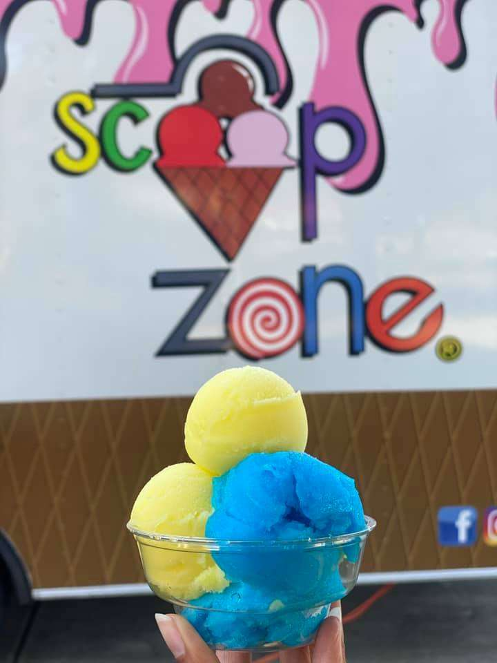 blue and yellow ice cream balls in a cup being held by a hand in front of the Scoop Zone truck.