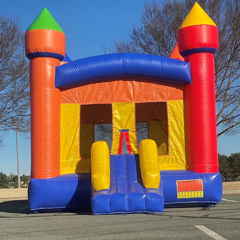 Castle shaped bounce house with red, blue, orange, and yellow parts, inflated and sitting in an empty parking lot.