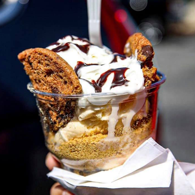 A hand holding a cup of ice cream with two chocolate chip cookies on the sides of the ice cream in the cup